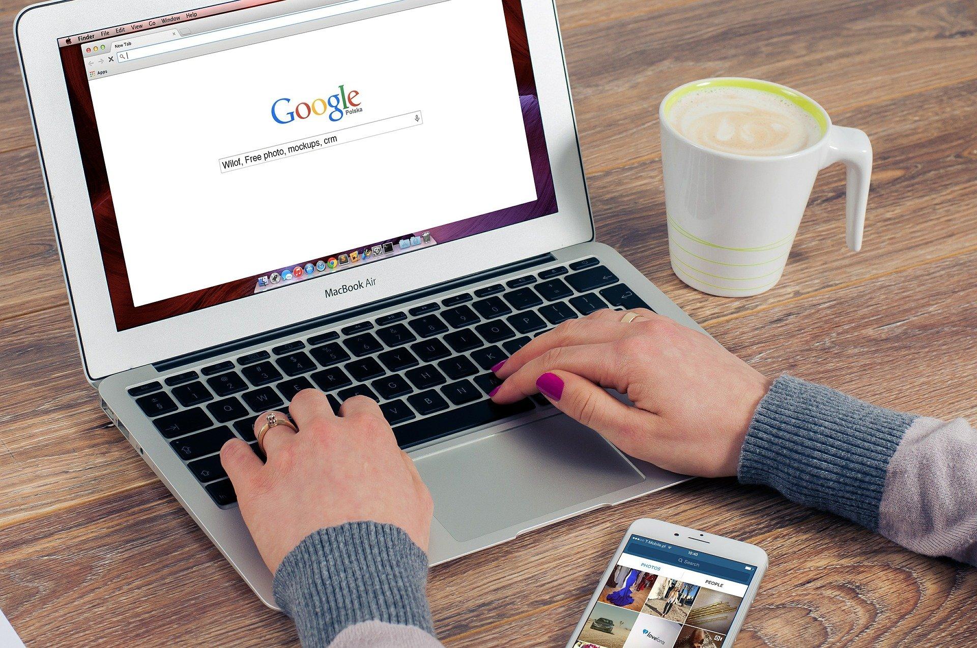 une dame tape une recherche sur un moteur de recherche sur son ordinateur portable